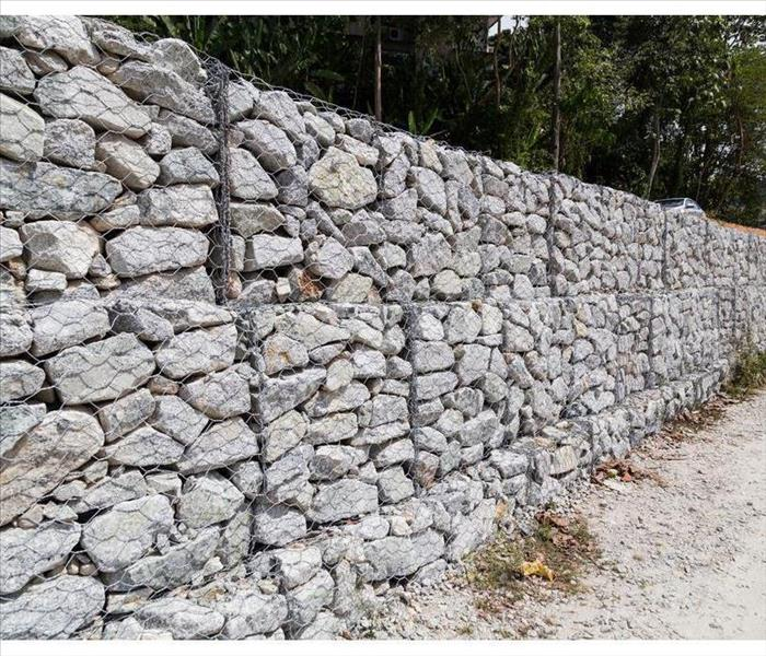 Slope and earth retention wall management with rocks and wire mesh cage system
