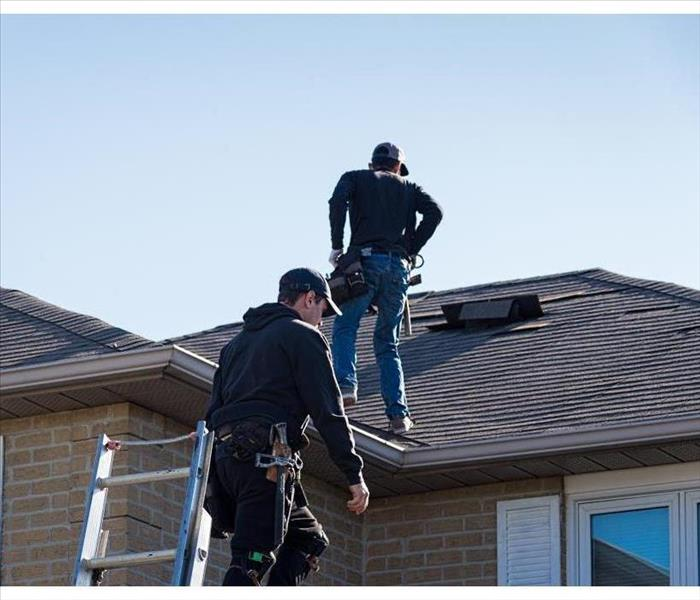 Two roofers inspecting a damaged roof