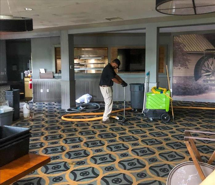 Worker using extracting vacuum on carpet floor, fire damage in a commercial building